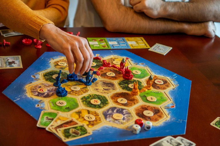 Board game party with my friends. Settlers of Catan, popular board game. Players are scrambling the area to get more resources and victory points.
