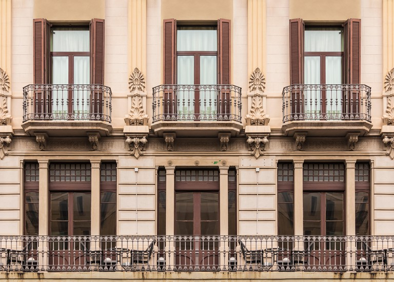 Several windows and balconies in a row on the facade of the urban historic building front view, Barcelona, Spain