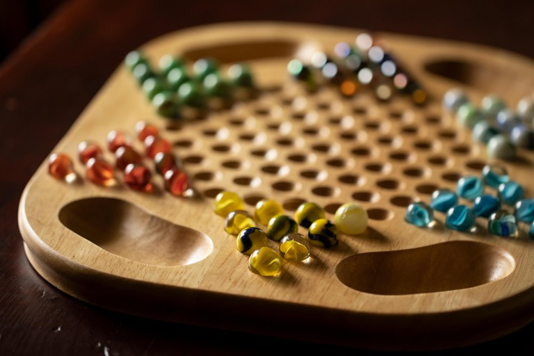 A wooden Chinese checkers game board with marbles of different colors, sitting on a cherry wood table.