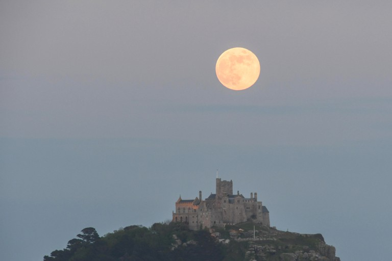Long Rock, Cornwall, UK. 18th May 2019. UK Weather. The full flower moon, also a blue moon, seen rising above St Michaels mount this evening. Credit Simon Maycock / Alamy Live News.