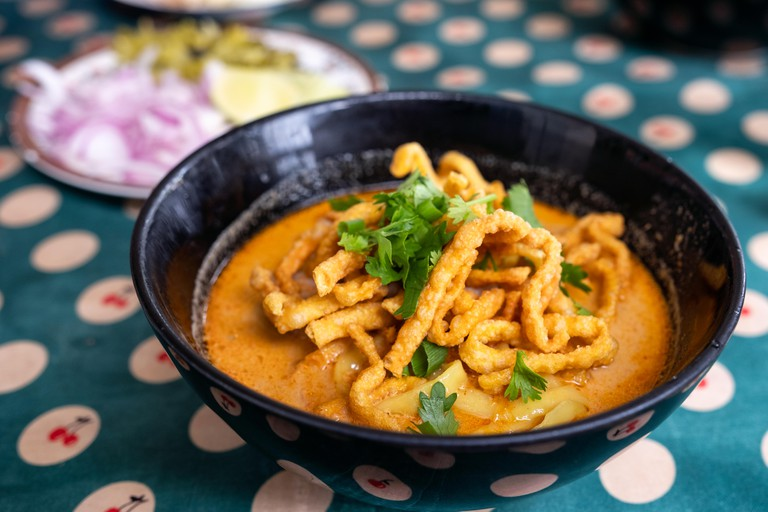 Northern Thai food of Coconut curry noodle soup with chicken (Khao Soi) in black bowl