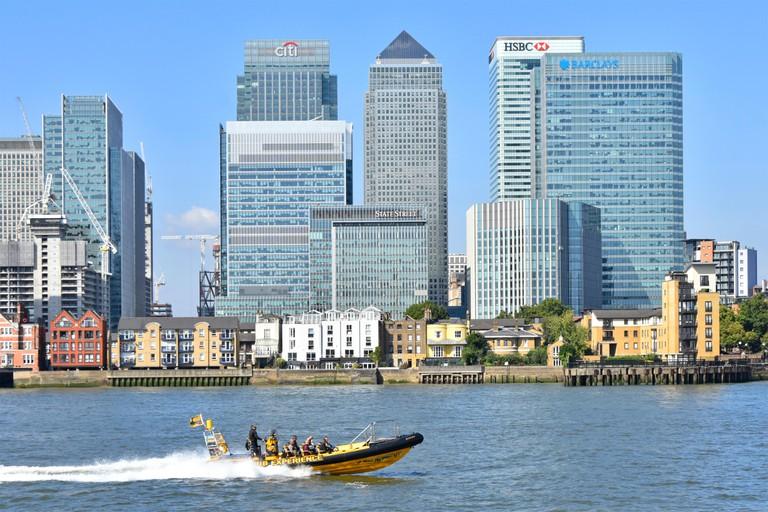 Thames Rib Experience tourists speedboat passing modern landmark skyscraper buildings on Canary Wharf Isle of Dogs London Docklands skyline England UK