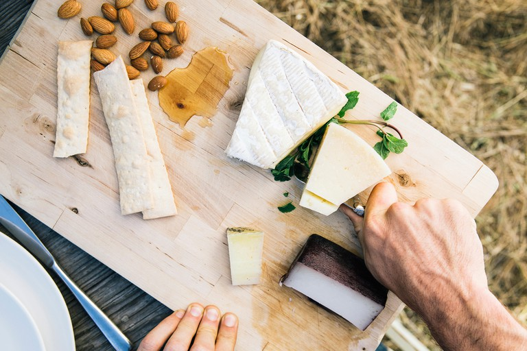 Overhead view of man cutting cheese on board