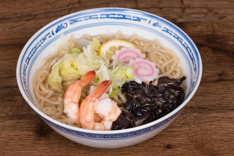 Ramen Shio with fish broth, shrimp, naruto Kamaboko,black mushrooms, Chinese cabbage, dark wood table background