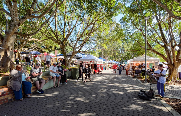 A young busker performing at the weekly market, in the popular small rural town of Eumundi, Queensland, QLD, Australia