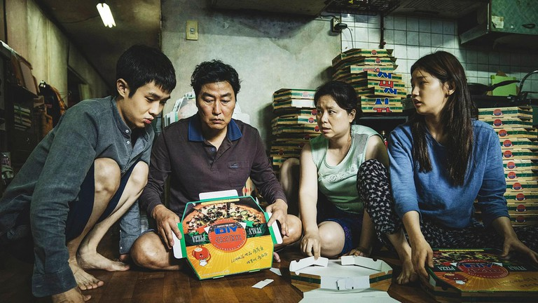 The Kim family folds pizza boxes in their subbasement apartment in the film Parasite, 2019
