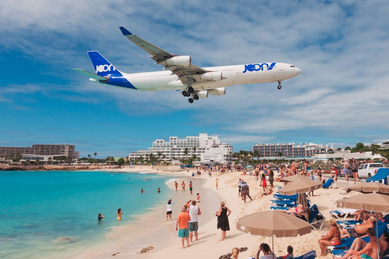 An Air France JOON Airbus A340-300 sails over tourists on Maho Beach, St. Maarten
