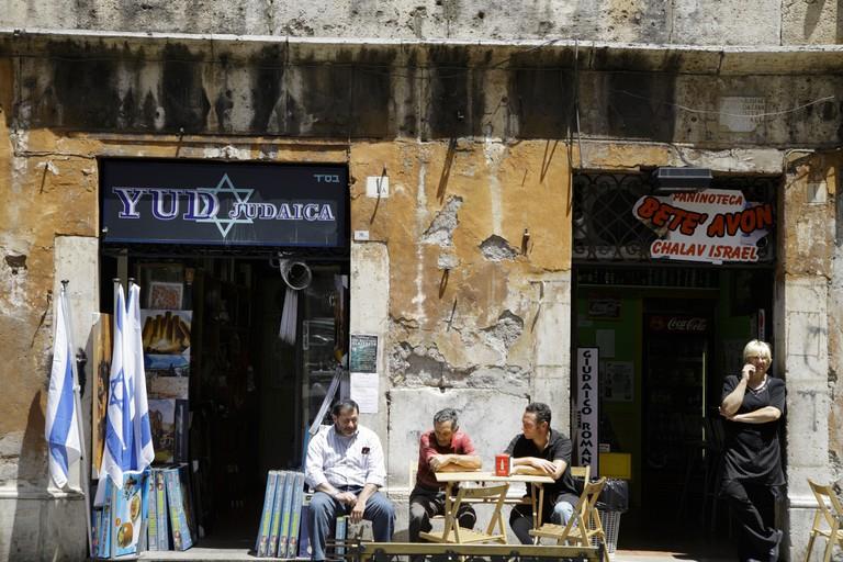 Street scene in the Rome ghetto Via del Portico d'Ottavia. People sitting outside shops in Rome Jewish quarter.
