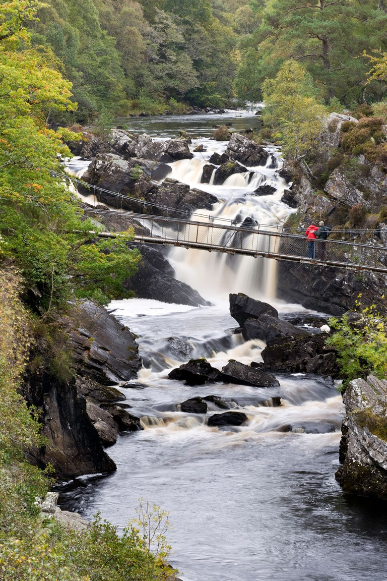 A couple look over a Suspended bridge over Rogie Falls near Inverness in Scotland.