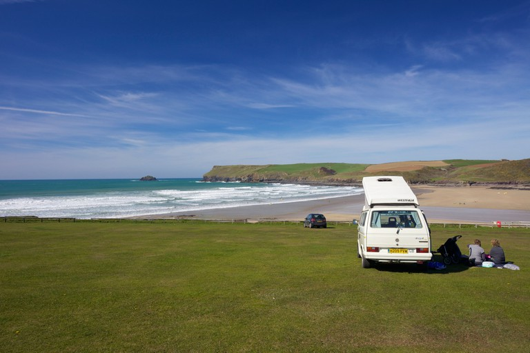Couple in camper van enjoying views across Polzeath beach to Pentire Headland North Cornwall England UK GB British Isles