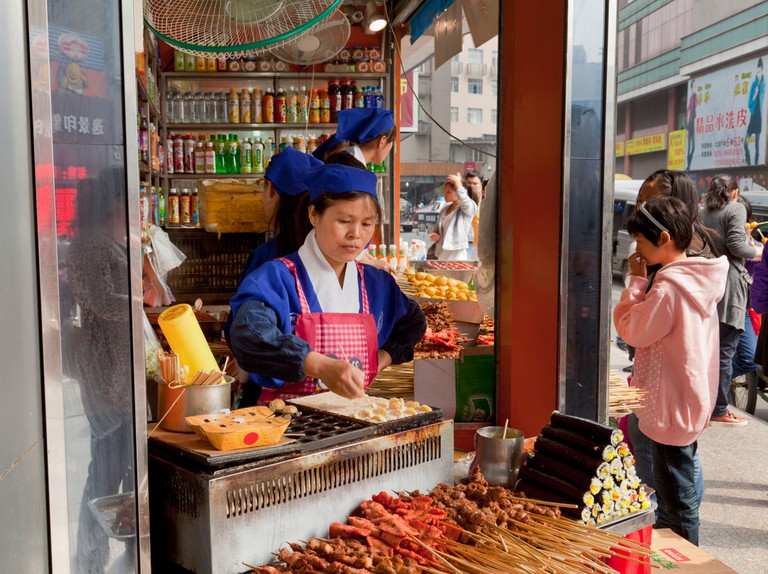 Woman selling freshly prepared snacks from a street corner stall in Chengdu.