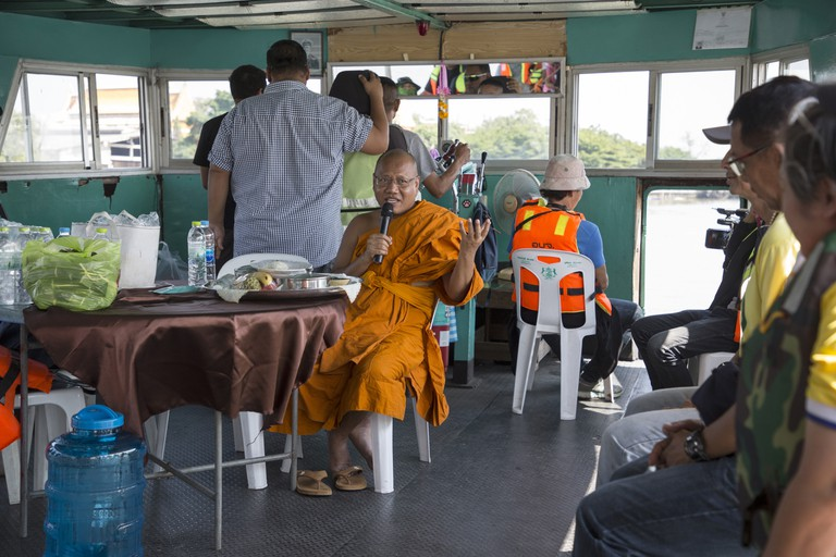 CH_Plastic_Cleanip-1080 - Phra Mahapranom Dhammalangaro, the Abbot of Chak Daeng Buddhist temple talks to volunteers on a boat who are taking part in a river clean-up event organised by the temple. Over 100 people will descend on to boats and retrieve garbage from the Chao Praya River that flows next to the temple. For over a decade this unique Thai Buddhist temple just outside Bangkok called Wat Chak Daeng has pursued ways to recycle waste particularly plastics. Under the guidance of Phra Mahapranom Dhammalangaro the temple has recycled everything from food waste to plastic bottles and began inviting people to join in their recycling activities to raise awareness about how people can recycle waste in every day life. From humble beginnings the temple started to attract attention when it began a project that recycled plastic bottles turning them in to saffron coloured monks robes which it continues to do today. Now, it receives daily deliveries of plastic bottles from across the country which adds up to 10 tonnes per month which it then recycles to make the robes and other clothing items.
