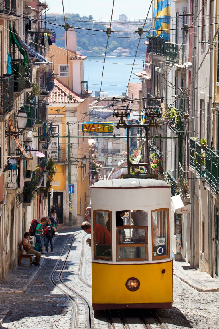 Tram of the Elevador da Bica funicular railway, overlooking the Rio Tejo River, in the district of Bairro Alto, Lisbon, Portugal