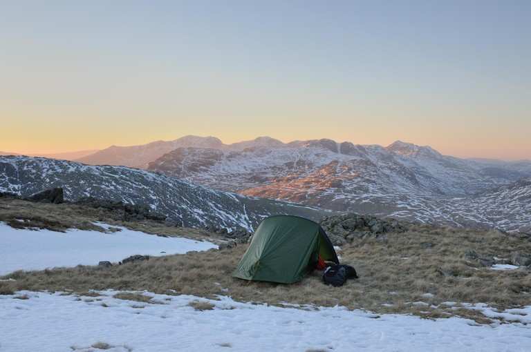 Wild camping on Wetherlam in winter in the English lake District, with Scafell Pike Crinkle Crags and Bowfell in the background