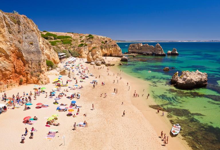 Travel Holidaymakers sunbathing on Praia da Dona Ana sandy beach near the resort of Lagos Algarve Portugal EU Europe