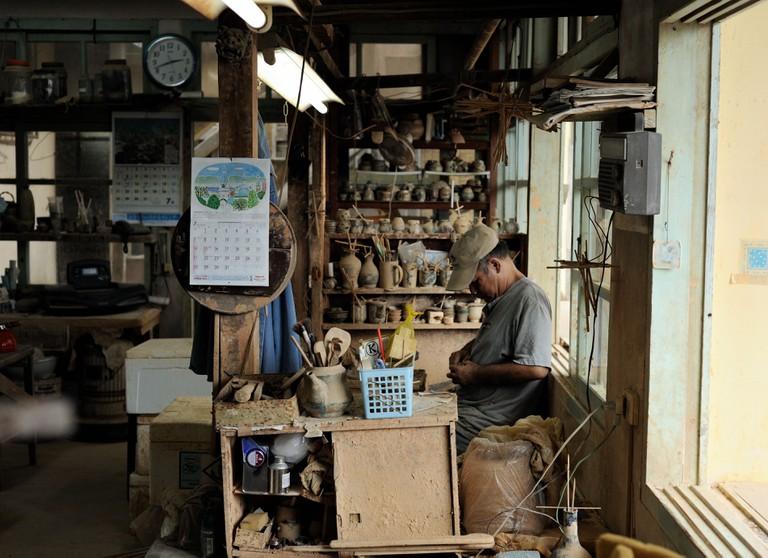 Tsuboya Pottery craftsman hard at work in Naha City, Okinawa, Japan.