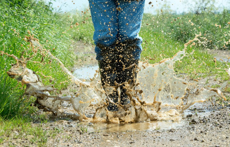 Man in wellington boots jumping in a puddle of water on a track in the english countryside
