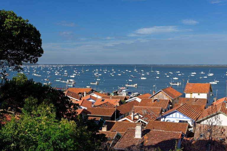 France, Gironde, Arcachon Bay, L'Herbe, view of a fishing village with boats in the background
