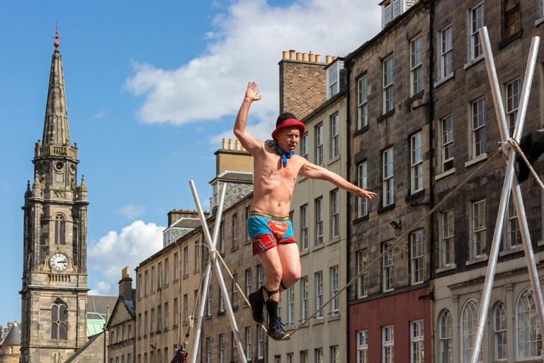 Trapeze artist performing on the Royal Mile during the Edinburgh Fringe Festival, Edinburgh, Scotland, UK