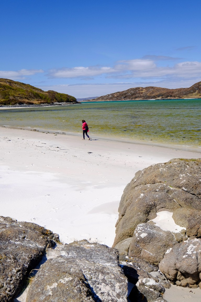 Woman walking on The 'Silver Sands of Morar' in the Scottish Highlands on the North West Coast close to Mallaig