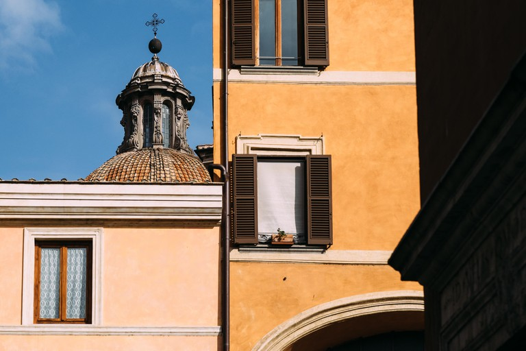 Colorful buildings, a bright blue sky and a tiled church cupola in the Ghetto neighbourhood of Rome, Italy