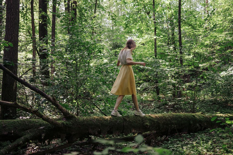 woman walking through a tree in the forest