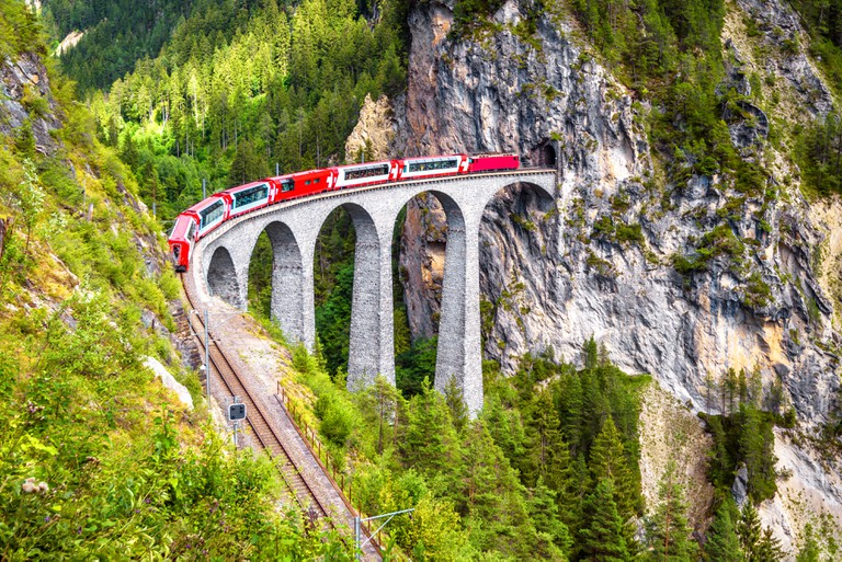 Bernina Express on a railroad bridge in the mountains, Switzerland.