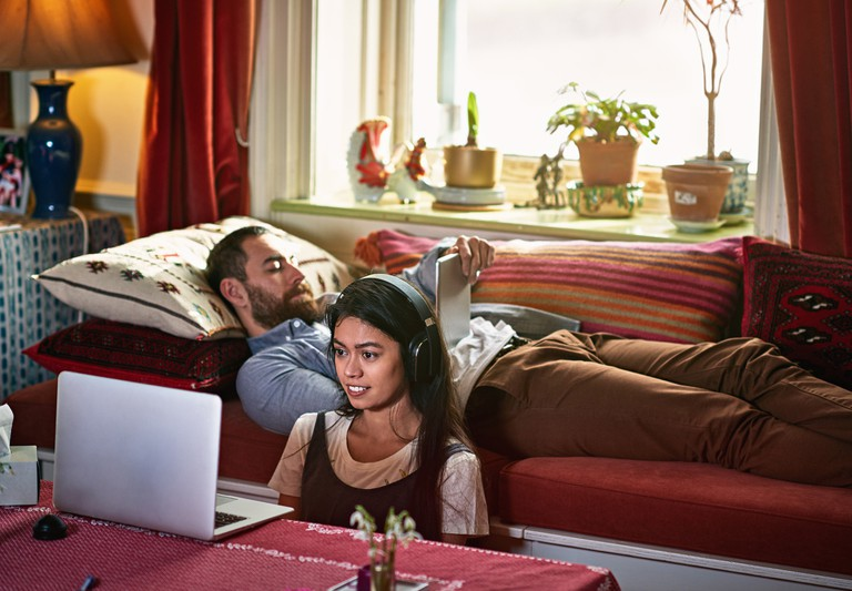 Couple together one with iPad one watching laptop