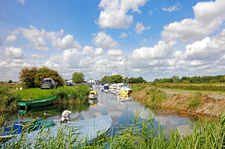 A dyke with moored boats off the River Thurne in the Broads National Park at Martham, Norfolk, England, United Kingdom.