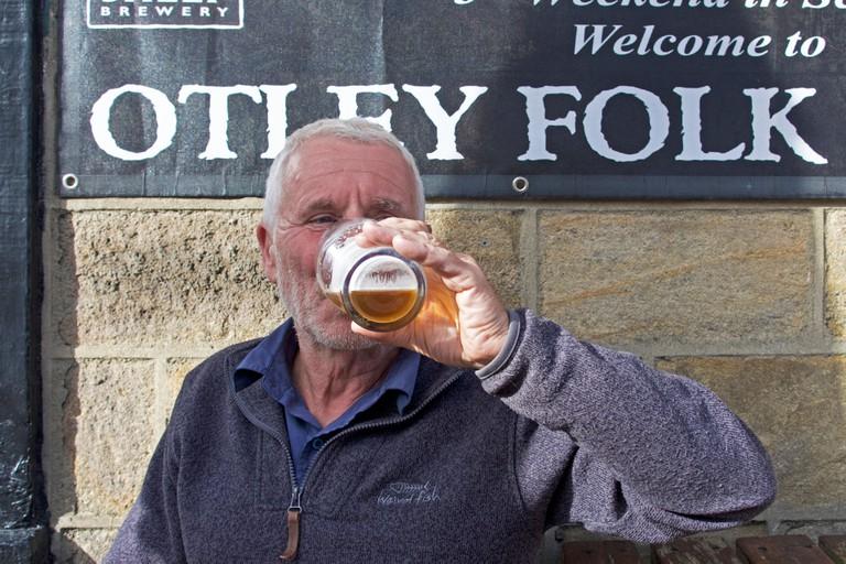 Man drinking beer at Otley Folk Festival, West Yorkshire, England UK