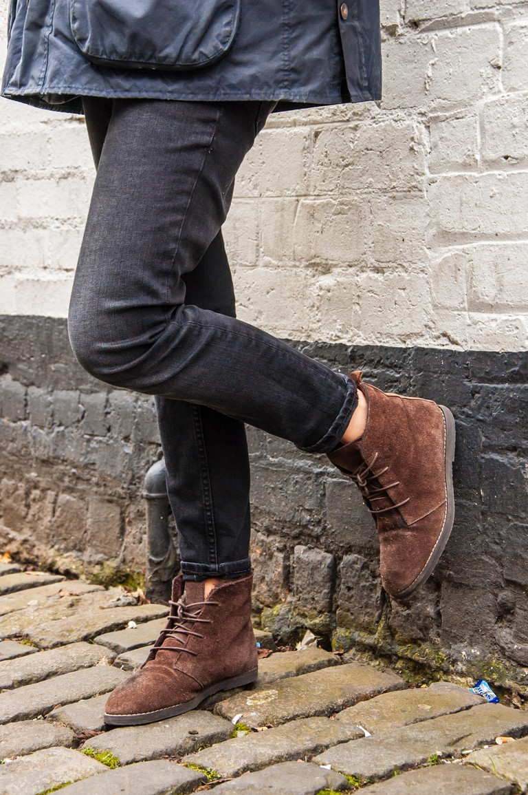 Model legs wearing tight black skinny trousers and brown ankle boots. Black and white brick wall as a background.