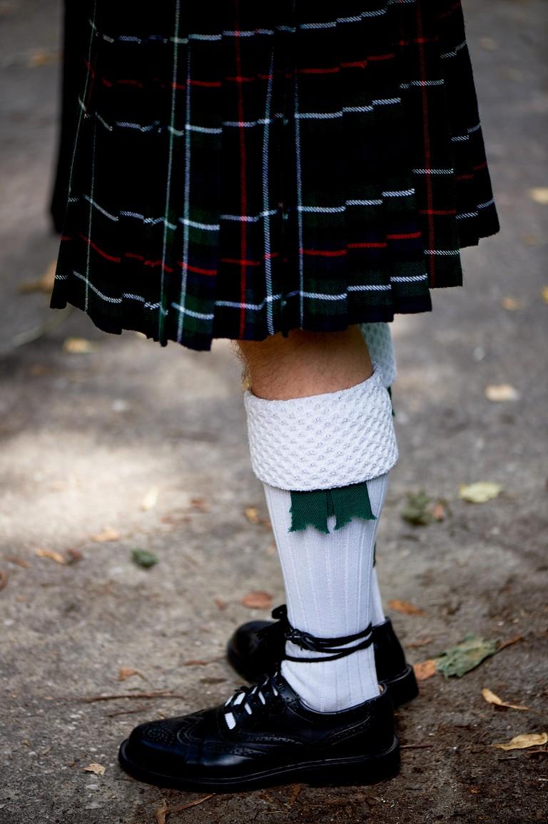 White socks and plaid Scottish kilt skirt. Culture
