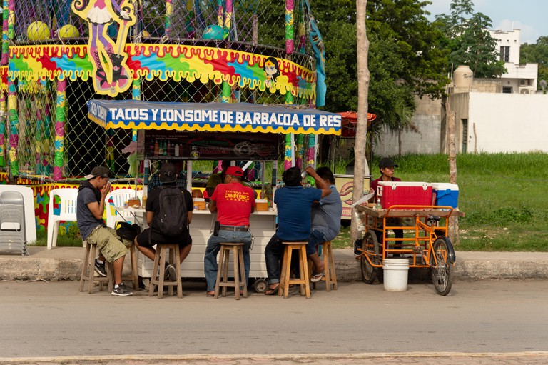 People eating tacos at a colorful mexican food stand
