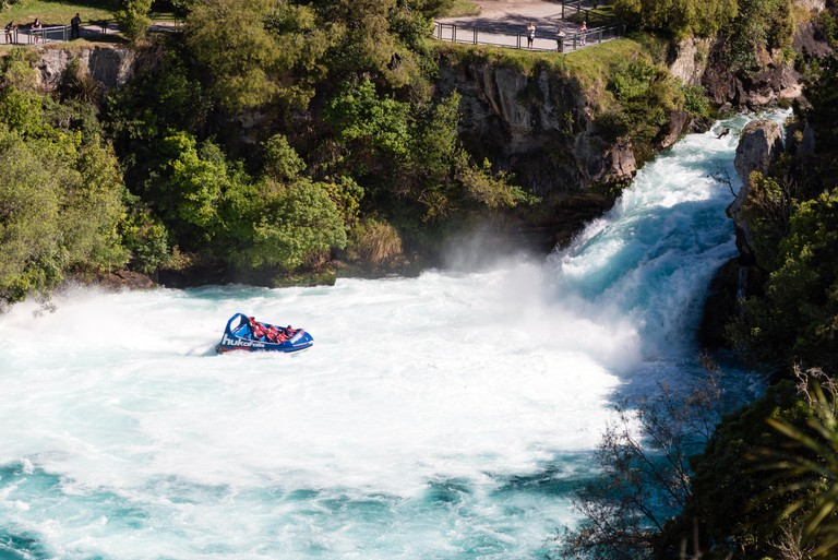 A jet boat with tourists races close to Huka Falls, New Zealand.