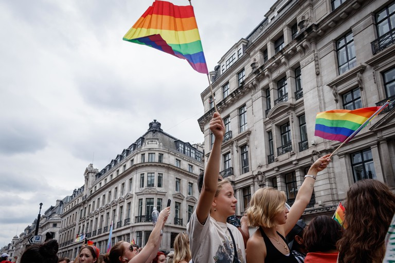 People waving rainbow flags during the parade.The Pride in