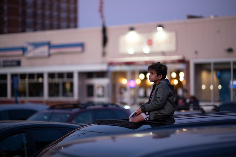 A boy sits on a car at drive-in event