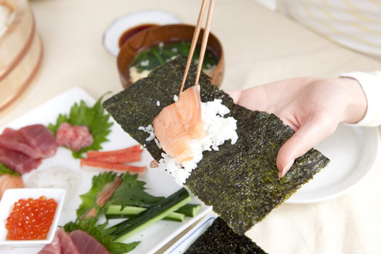Woman making hand-rolled sushi