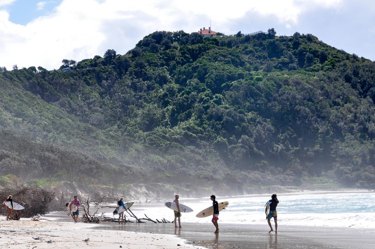 Surfers standing on the beach holding their surfboards at Tallow Beach, Byron Bay, NSW, Australia.