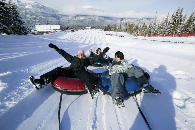 Family fun at the Blackcomb Mountain tube park; Whistler, British Columbia, Canada