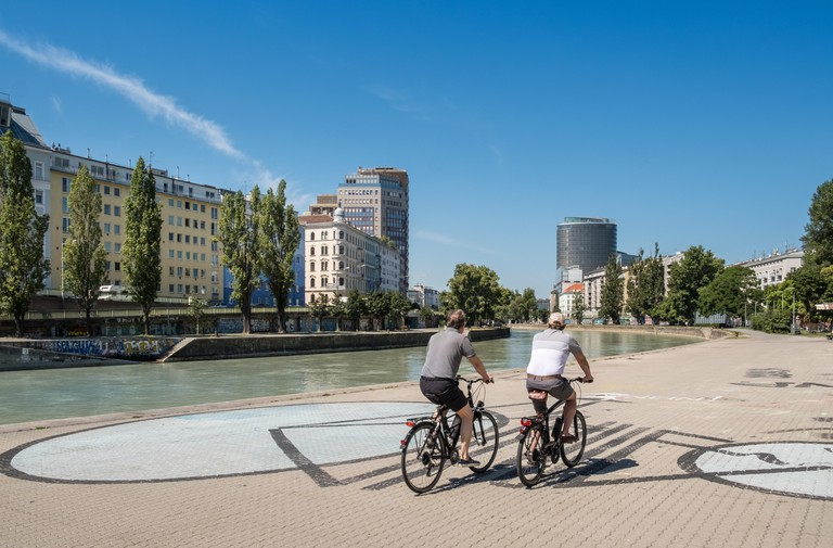 People cycling alongside the Danube Canal (Donaukanal) in the centre of Vienna, Austria