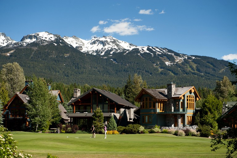 Golfers on the Whistler Nicklaus North golf course play in from of a row of link side houses, with Blackcomb Mountain the background.  Whistler BC