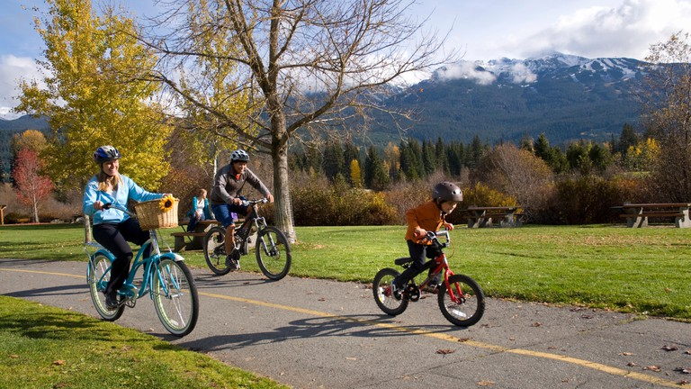 A family bikes along the trail near Meadow Park Recreation Centre, along the River of Golden Dreams. Whistler Mountain rises in