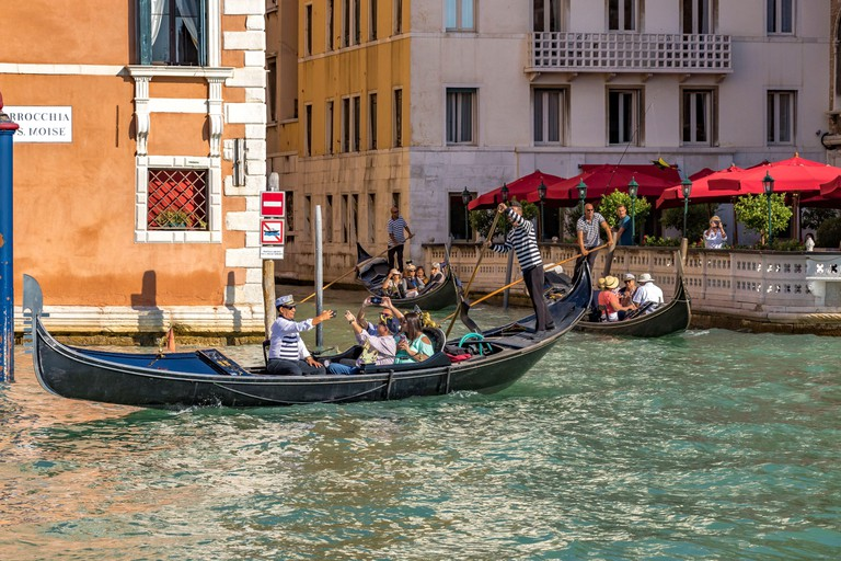 Tourists taking selfies on a gondola ride in Venice, Italy