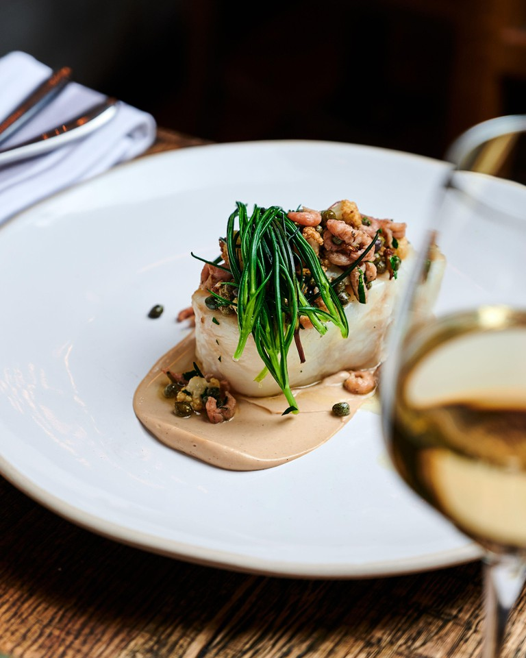 Cornish cod fillet with brown shrimps and cauliflower paste, served in a white plate at a michelin stared restaurant