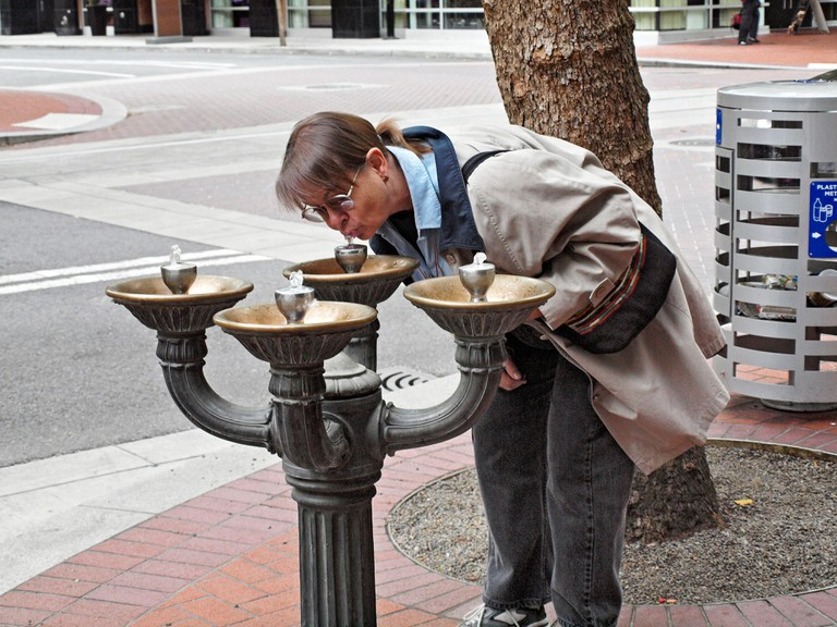 A mature woman drinks from fountain on downtown sidewalk in Portland Oregon  Known as Benson Bubblers these fountains unique to
