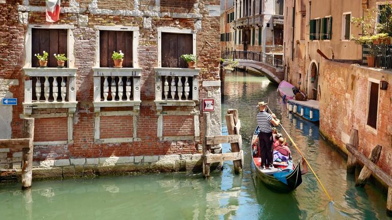 Gondolier flowing gondola, Venice canal