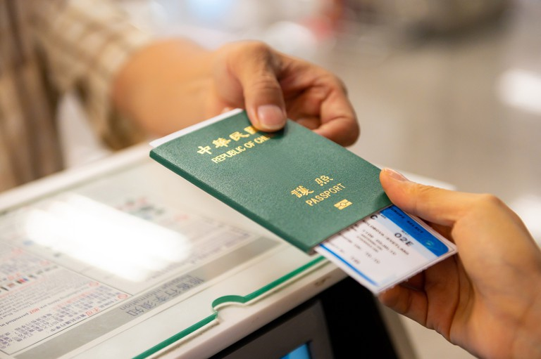 Stock image of passenger and CSR holding ticket with passport