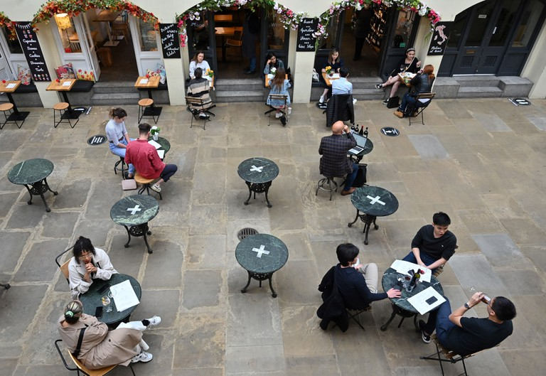 Customers sit at socially distanced tables in Covent Garden in London on July 4, 2020, as restrictions are further eased during the novel coronavirus COVID-19 pandemic