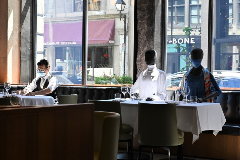 A server wearing a facemask adjusts glasses on a table next to mannequins placed at a table to provide social distancing at a restaurant in old Montreal