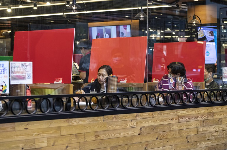 Plastic barriers on tables enforcing social distancing at a restaurant during the coronavirus pandemic in Hong Kong